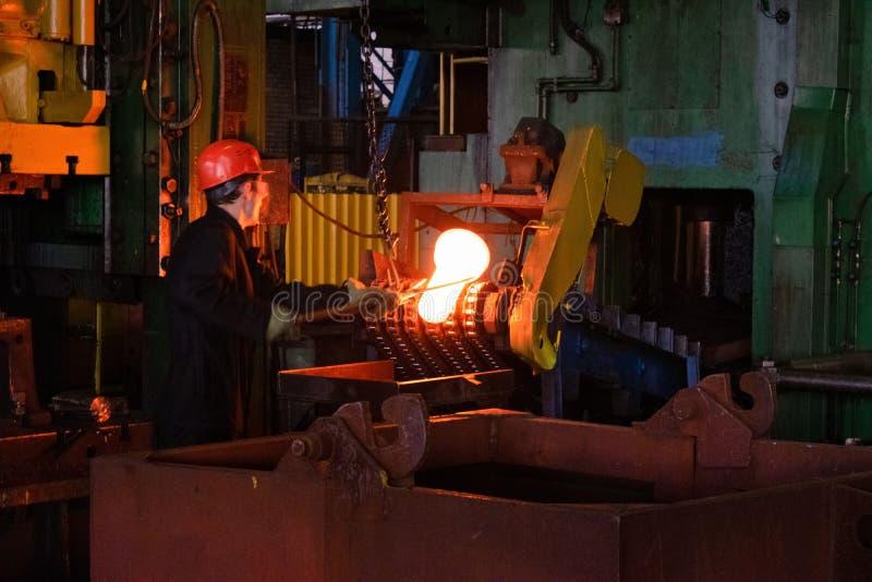 Schmied verarbeitet das Eisenprodukt unter einer enormen Presse und schmiedet das Metall und stempelt lizenzfreies stockfoto