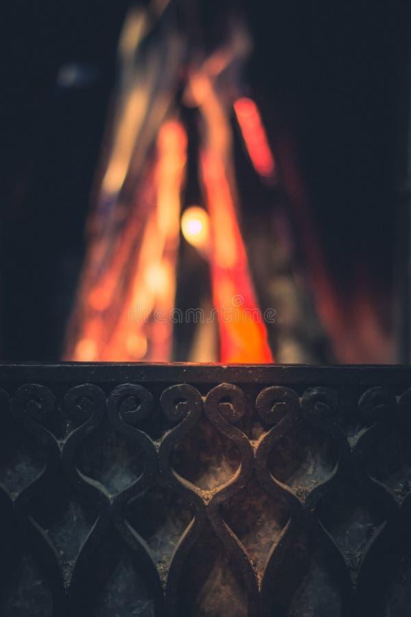 Schmiedeeisengrill auf dem Hintergrund eines brennenden Feuers im Kamin stockbilder