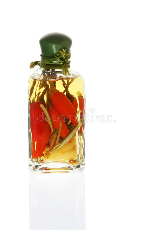 Schmieröl hineingegossen mit rote Paprika-Pfeffern lizenzfreie stockfotos