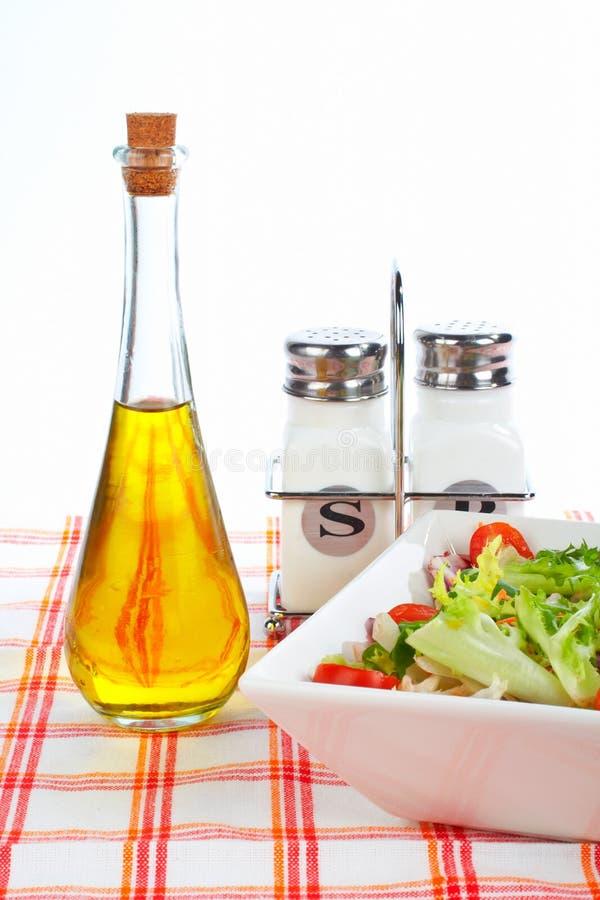 Schmierölflasche, grüner Salat, Salz und Pfeffer stockbild