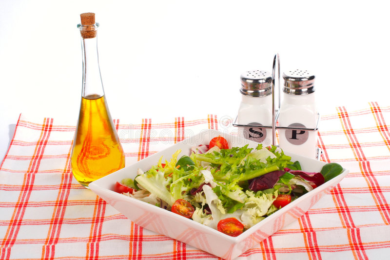 Schmierölflasche, grüner Salat, Salz und Pfeffer stockfotografie