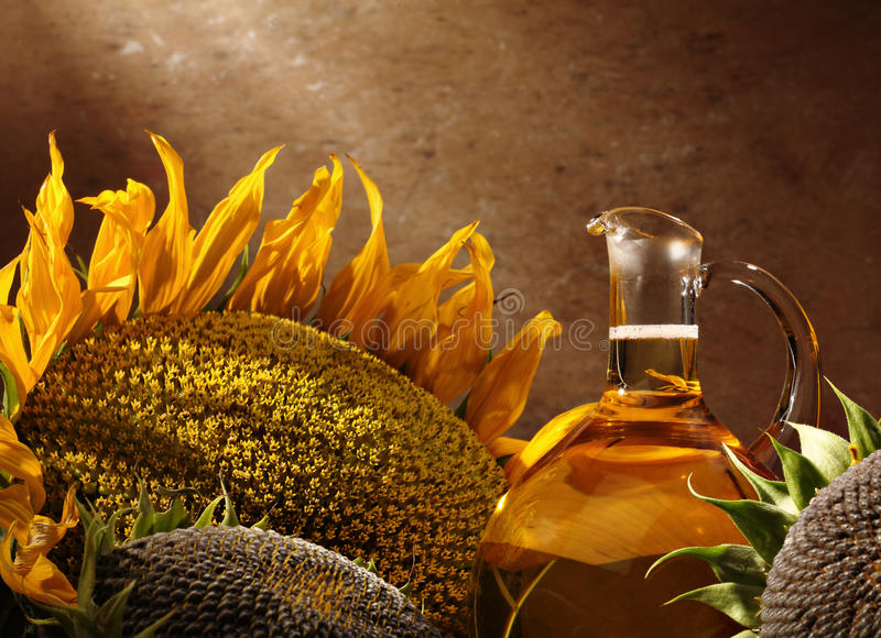 Schmierölflasche mit Sonnenblumen stockbilder