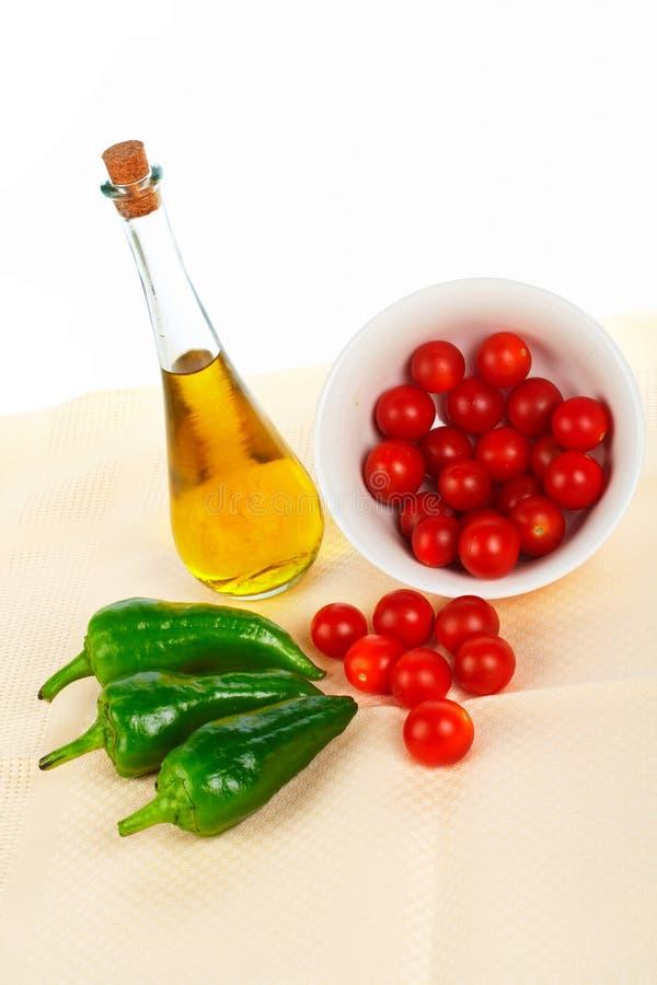 Schmierölflasche, rote Tomatekirsche und grüner Pfeffer stockbilder
