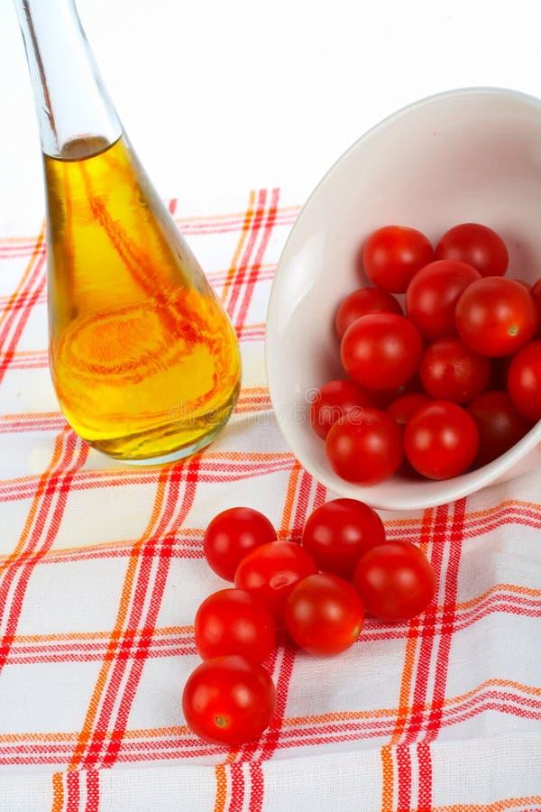 Schmierölflasche und Tomatekirsche stockfotografie