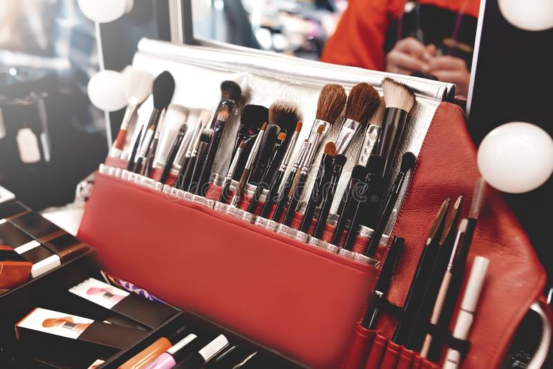 Schminkwerkzeuge schließen Schminkbürsten in Röhren, Ledertasche auf einem Holztisch Set verschiedener Objekte zum Make-up stockbild