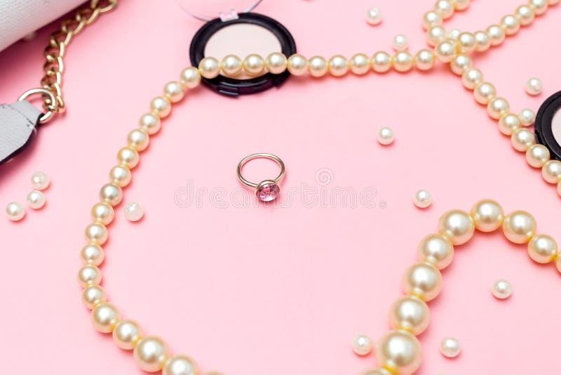Schmuck und Kosmetik auf einem rosa Hintergrund Weibliches Zubehör lizenzfreie stockfotografie
