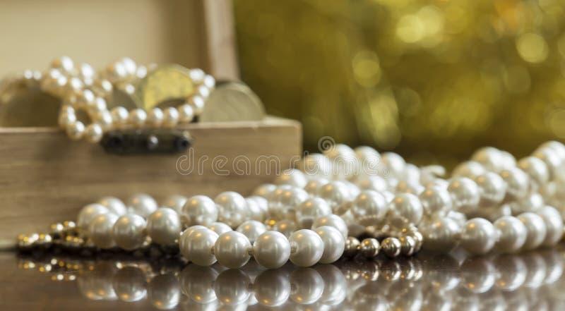 Schmucke, weiße Perlen mit Schatztruhe auf goldenem Hintergrund stockbild