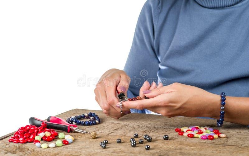 Schmuckherstellung Herstellung des Armbandes von den mehrfarbigen Perlen auf einem rauen hölzernen lizenzfreies stockbild