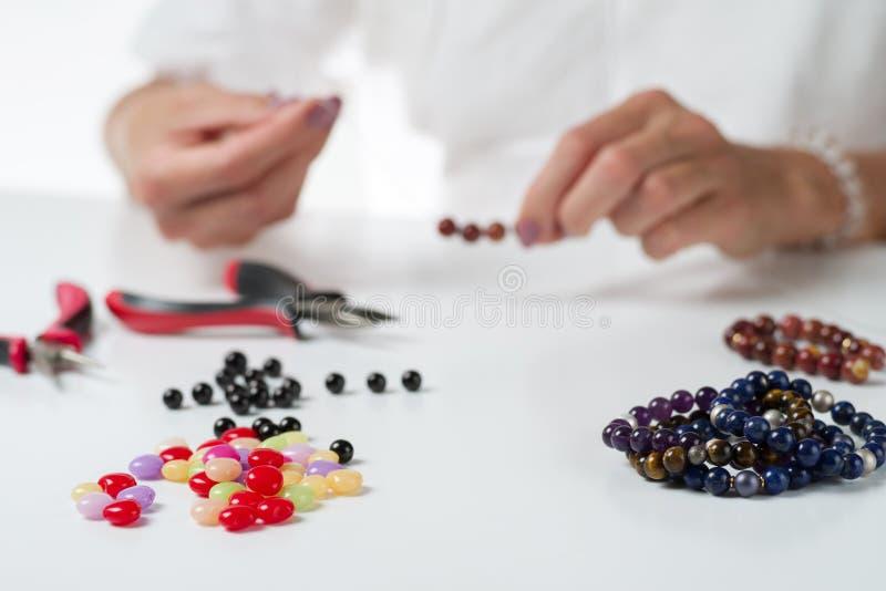 Schmuckherstellung Produktionsarmbänder und -halsketten von den mehrfarbigen Perlen lizenzfreie stockbilder