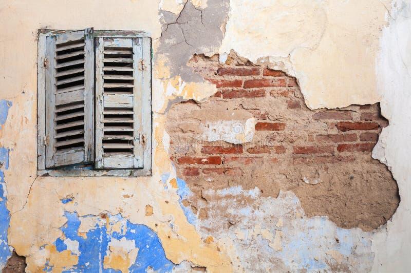 Schmutz schädigende Backsteinmauer mit geschlossenem Fenster stockbild