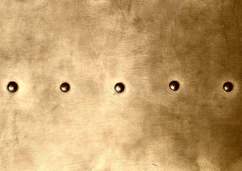 Schmutzgoldbraunmetallplatte befestigt Schraubenhintergrundbeschaffenheit lizenzfreie stockfotos
