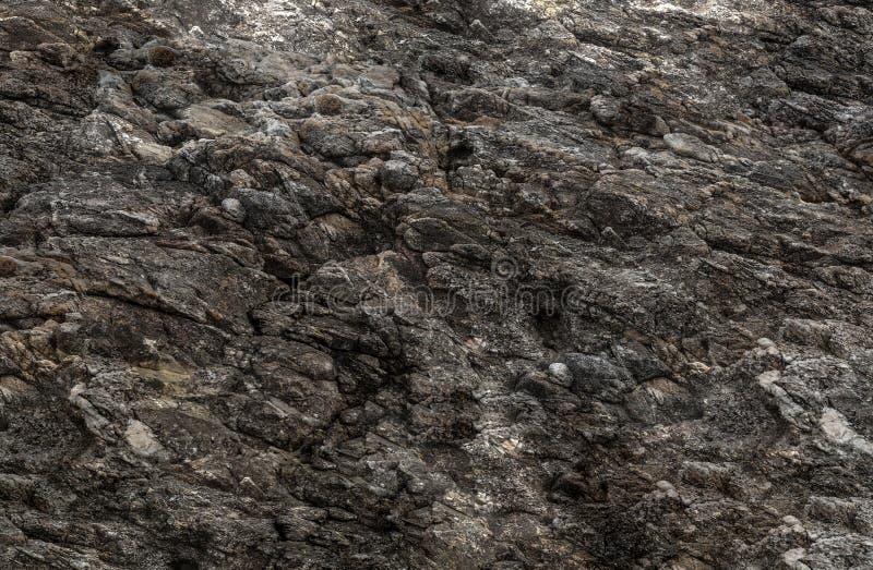 Schmutzhintergrundbeschaffenheits-verwitterten alte Steinwandschlaglöcher, natürliches Oberflächenteil eines dunklen Berges lizenzfreie stockfotografie