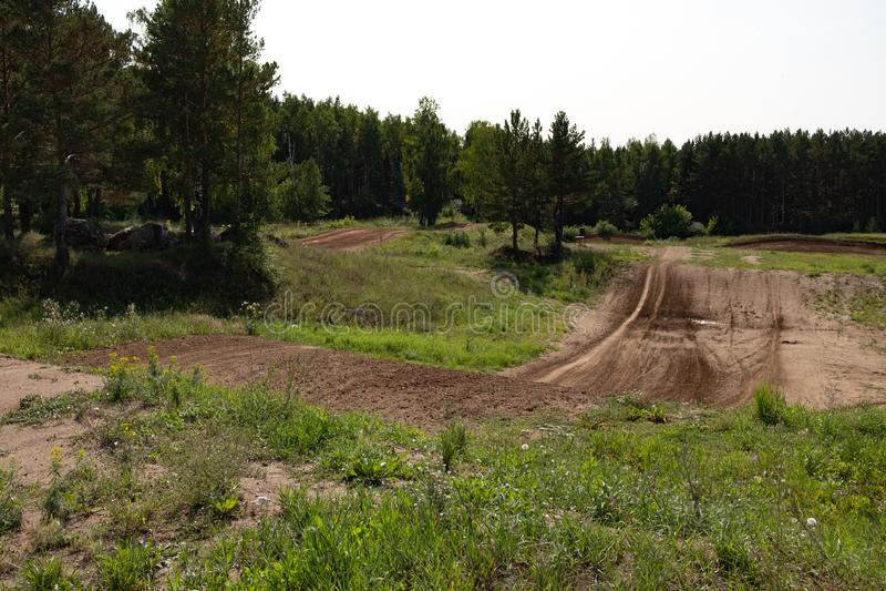 Schmutzige Bahn für Sporttätigkeiten von Motorradfahrern und von Buggy, Waldweg mit Hügeln stockfotos