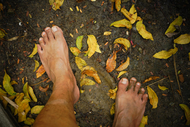Schmutzige bloße Füße, die auf dem Boden treten stockbild