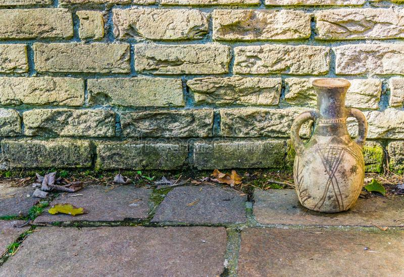 Schmutzige gelbe Backsteinmauer mit einer alten historischen schauenden Urne und Steineiner pflasterungshintergrundbeschaffenheit stockfotos
