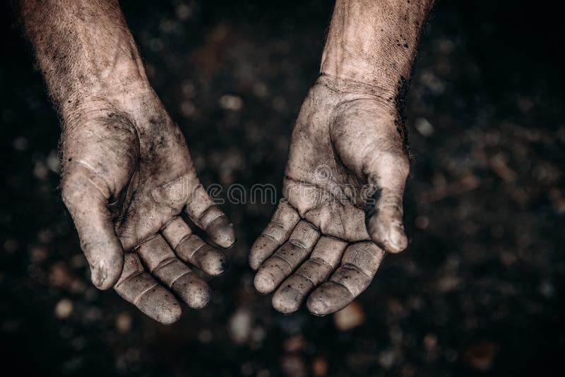 Schmutzige Hände des Arbeitskraftbergmannes sind Kornpalmen in den Abnutzungen Harte Arbeit des Konzeptes stockfotos
