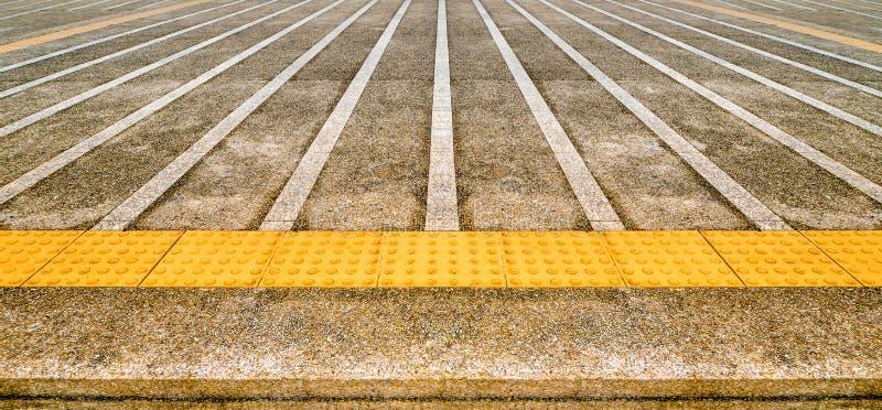 Schmutzige konkrete Bahn mit gelbem Tast stockbilder