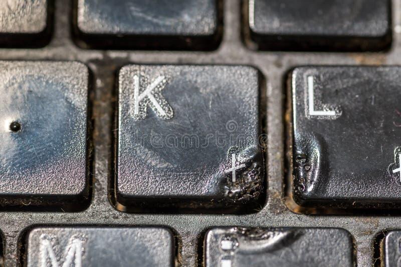 Schmutzige schwarze dünne Tastatur vom Laptop oder vom Tischrechner mit geschmolzenen Plastikschlüsseln von den Zigaretten-Brandw stockfoto