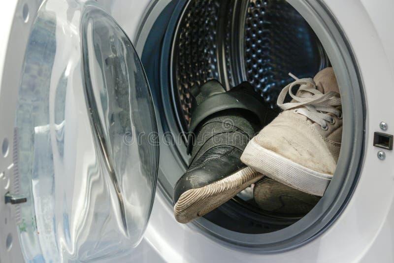 Schmutzige Schwarzweiss-Turnschuhe in der Waschmaschine stockbild