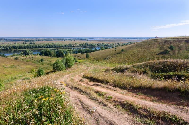 Schmutzige Straße des Landes führt durch Hügel zu einen Fluss stockbild