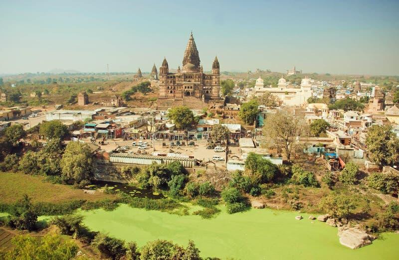 Schmutziger Green River und großer hindischer Chaturbhuj-Tempel in der indischen Stadt stockbilder