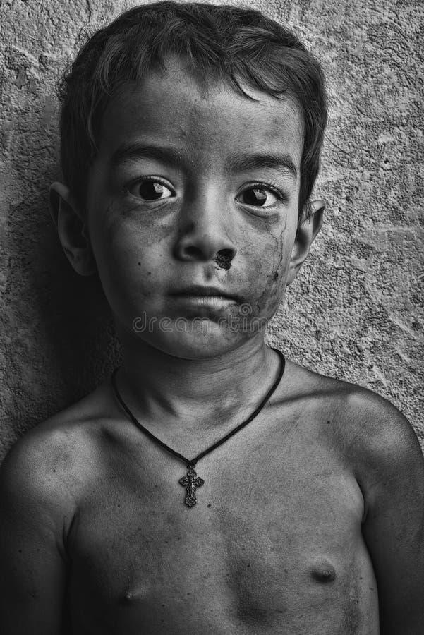Schmutziger Junge auf einem Hintergrund der grauen Wand mit einem Ausdruck der Verzweiflung auf seinem Gesicht stockbilder