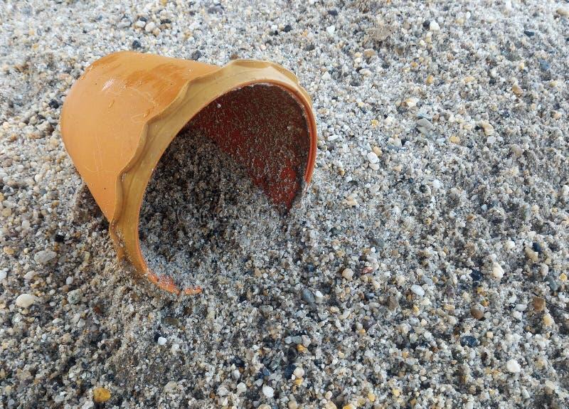 Schmutziger orange Topf auf Sand für Hintergrund lizenzfreie stockfotos