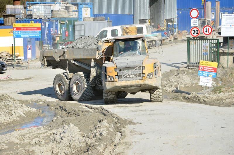 Schmutziger schwerer Volvo-Kipper lud durch den Felsen, der im Arbeitsstandort sich bewegt Es gibt den Slovak Landstraße beschrif lizenzfreie stockfotografie