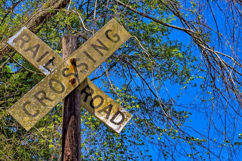 Schmutziges Eisenbahnüberfahrtzeichen auf hölzernem Beitrag lizenzfreie stockfotos