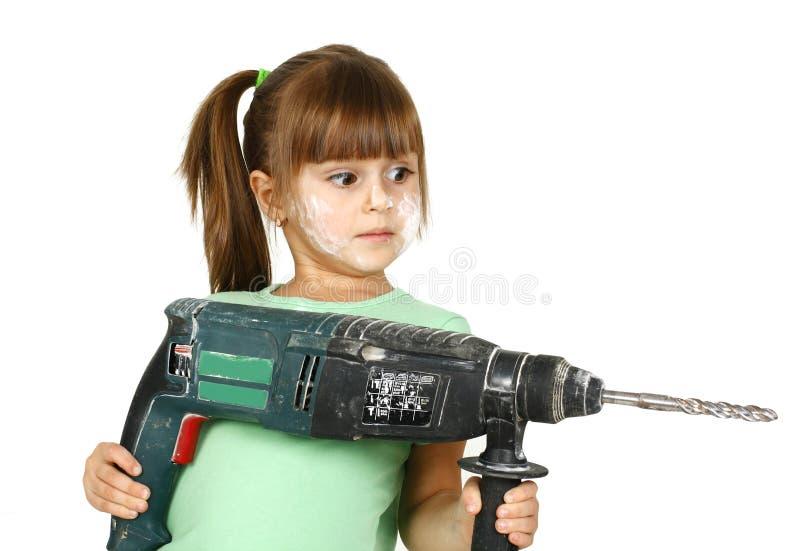 Schmutziges Kindmädchen mit elektrischem Bohrgerät stockfotografie