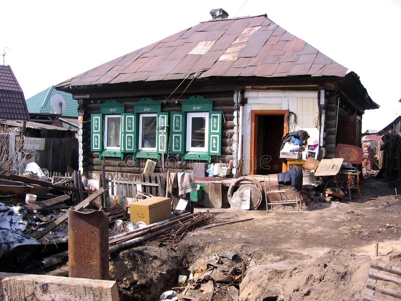 Schmutziges zerzaustes Bordell des Holzhauses mit russischem Dorf des Abfalls und des Schlammes in Sibirien lizenzfreies stockbild