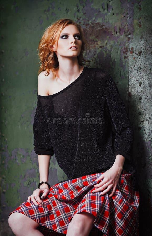 Schmutzmode: Porträt des informellen Modells des schönen jungen Rothaarigemädchens im Plaidrock und -bluse stockfotografie