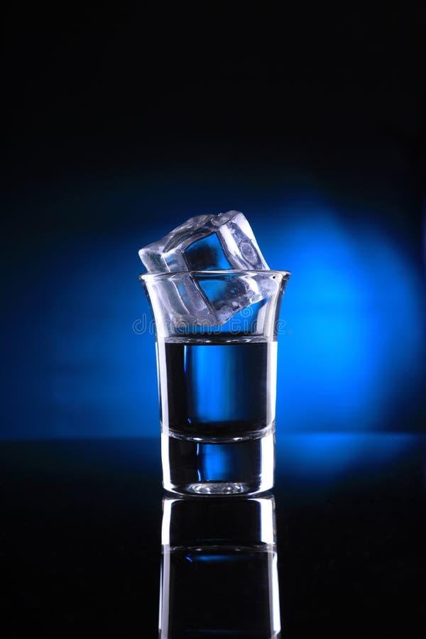 Schnapsglas mit einem Eis-Würfel auf blauem Hintergrund stockfotos