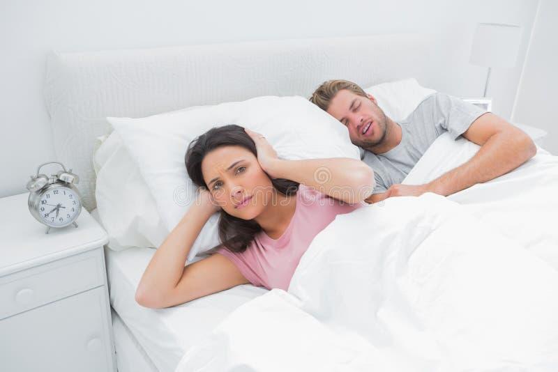Schnarchender Mann stört seine Frau, die versucht zu schlafen stockfoto