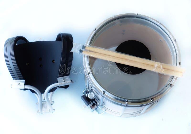 Schnarrtrommel, ein Stoßgerät mit 2 Gesichtern ausgedehnt mit Trommeln und Trommelstöcken, ein weißer Hintergrund stockbilder