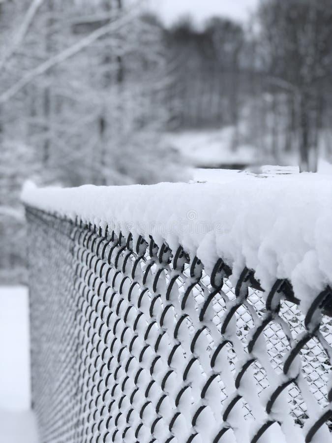 Schnee überstieg Zaun mit schneebedecktem Hintergrund lizenzfreie stockfotografie