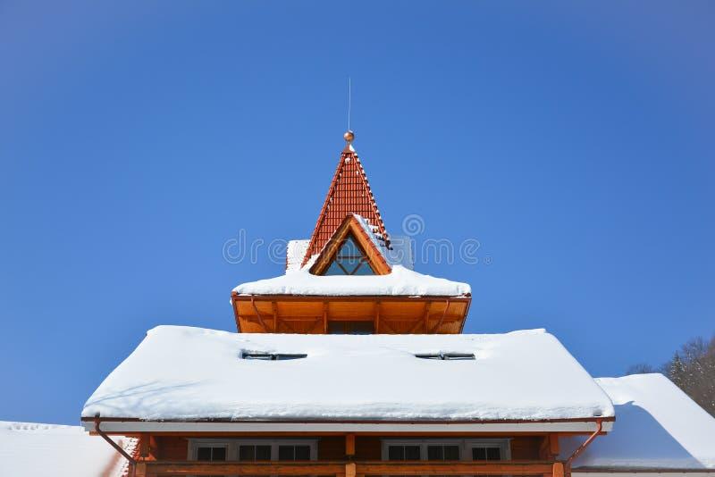 Schnee auf dem Dach des Holzhauses Dachbodenfenster des dreieckigen sha stockfotografie