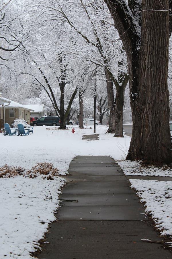 Schnee bedeckt teilweise Bürgersteig nach Schneefällen stockfotografie