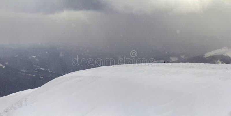 Schnee bedeckte Karpatengebirgshügel mit weit weg Wandererausflug stockfoto