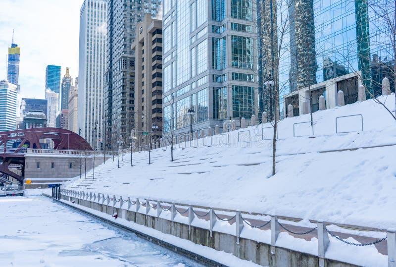 Schnee bedeckte Treppe auf dem Chicago Riverwalk mit dem Fluss, der im Winter eingefroren wurde lizenzfreies stockbild