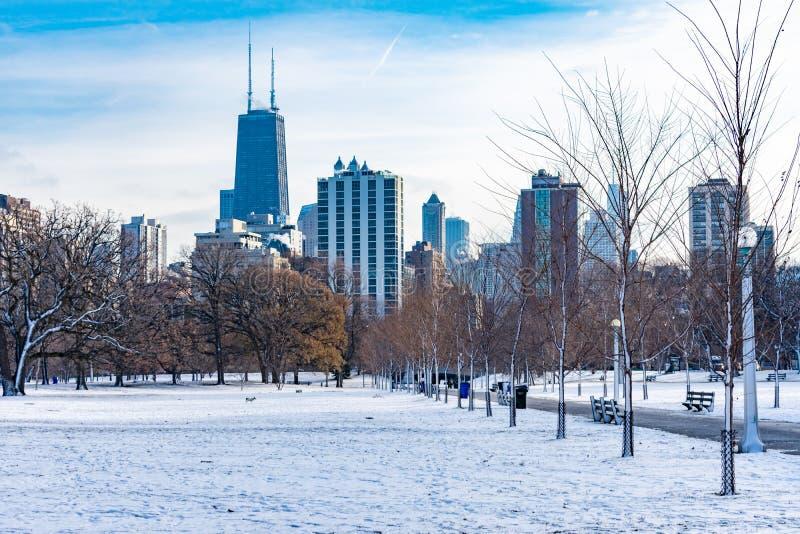 Schnee bedeckter Park in Chicago mit Skylinen stockbilder