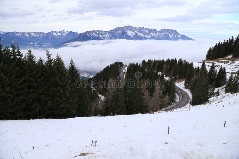 Schnee in den österreichischen Alpen mit kurvenreicher Straße lizenzfreie stockbilder
