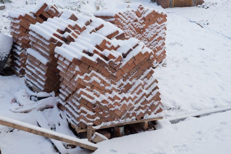 Schnee fällt und bedeckt Paletten mit den roten Backsteinen und steht im Yard im Winter stockfoto