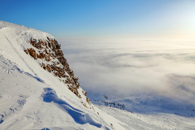 Schnee fror in interessanten Beschaffenheiten und in Eiszapfen nach dem Felsen entlang der Klippe und dem starken Nebel an einem  lizenzfreie stockfotos