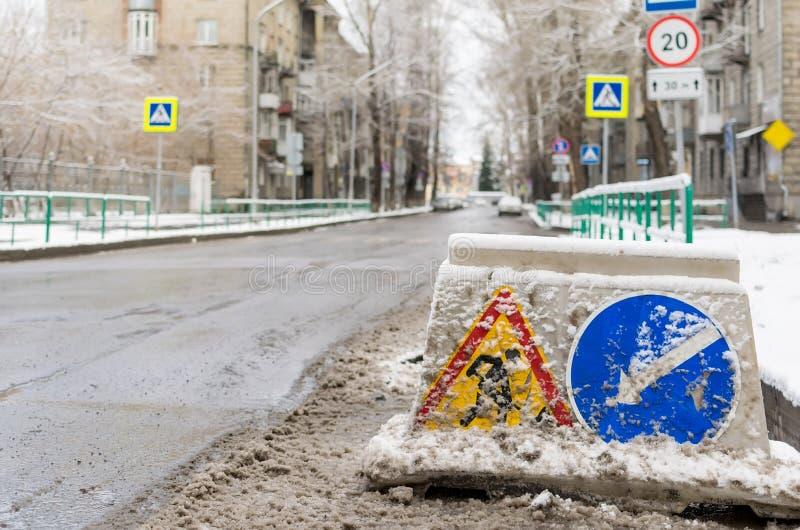 Schnee-gefegtes Verkehrsschild, Straßenreparatur, Stände auf der Fahrbahn lizenzfreie stockfotografie