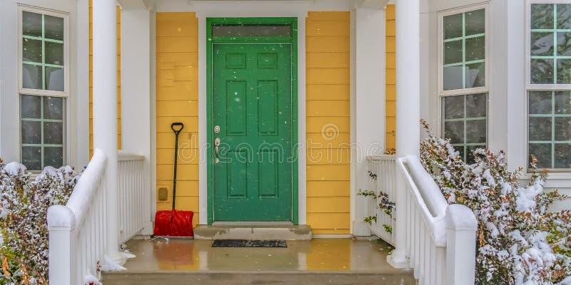 Schnee showel neben der grünen Haustür eines Hauses lizenzfreie stockfotografie