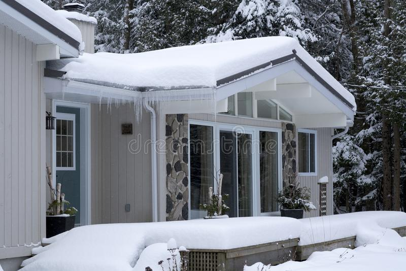 Schnee und Eis auf Dachspitzen-Gossen lizenzfreies stockbild