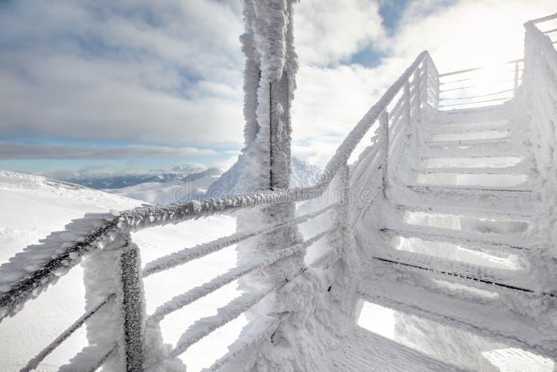 Schnee und Eis bedeckten Treppe, mit starker Sonnenhintergrundbeleuchtung stockbilder
