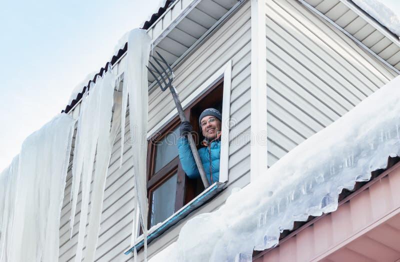 Schnee-und Eiszapfen-Abbau vom Dach stockfoto