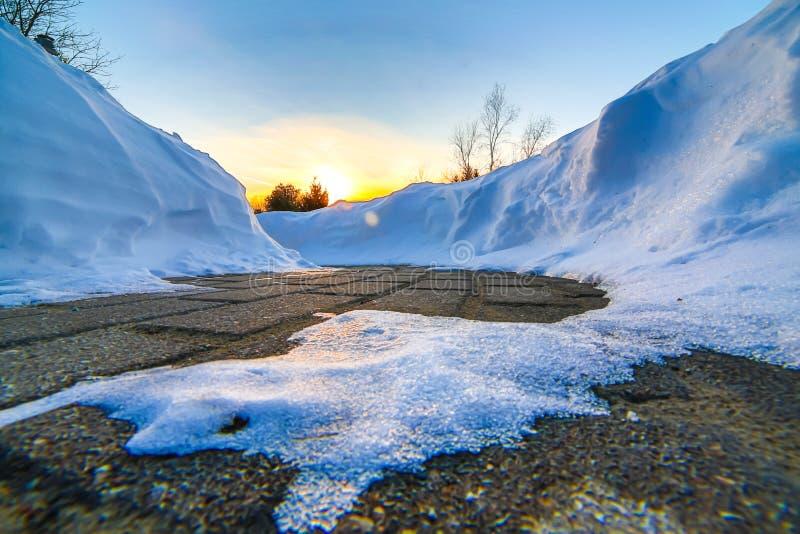 Schneebanken auf Gehweg bei Sonnenuntergang im Winter stockfotos